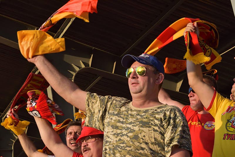 A Tulsa fan waves a red and yellow scarf in the air at a football match. The man is wearing a green, camouflage-print t-shirt, baseball cap and aviator sunglasses.