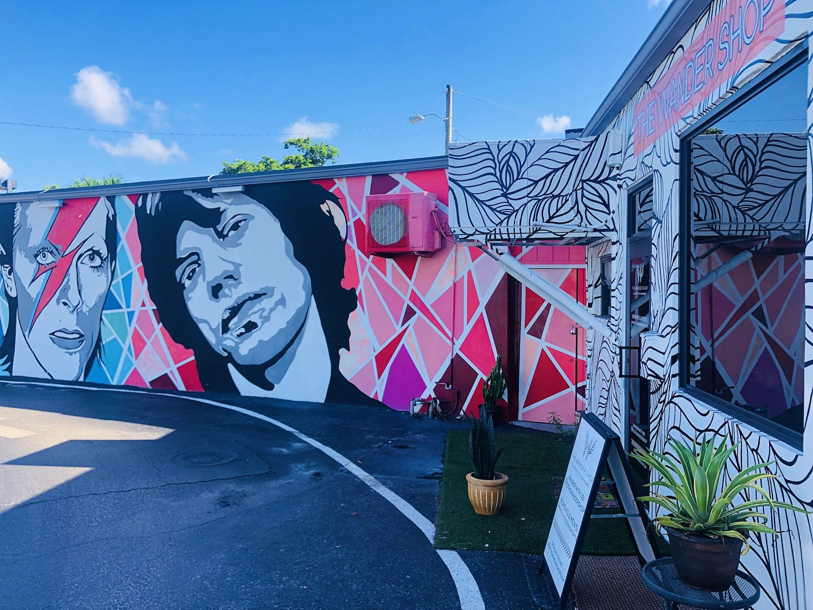 A mural of David Bowie and Mick Jagger in pink, grey and purple shades covers a wall next to a small boutique.