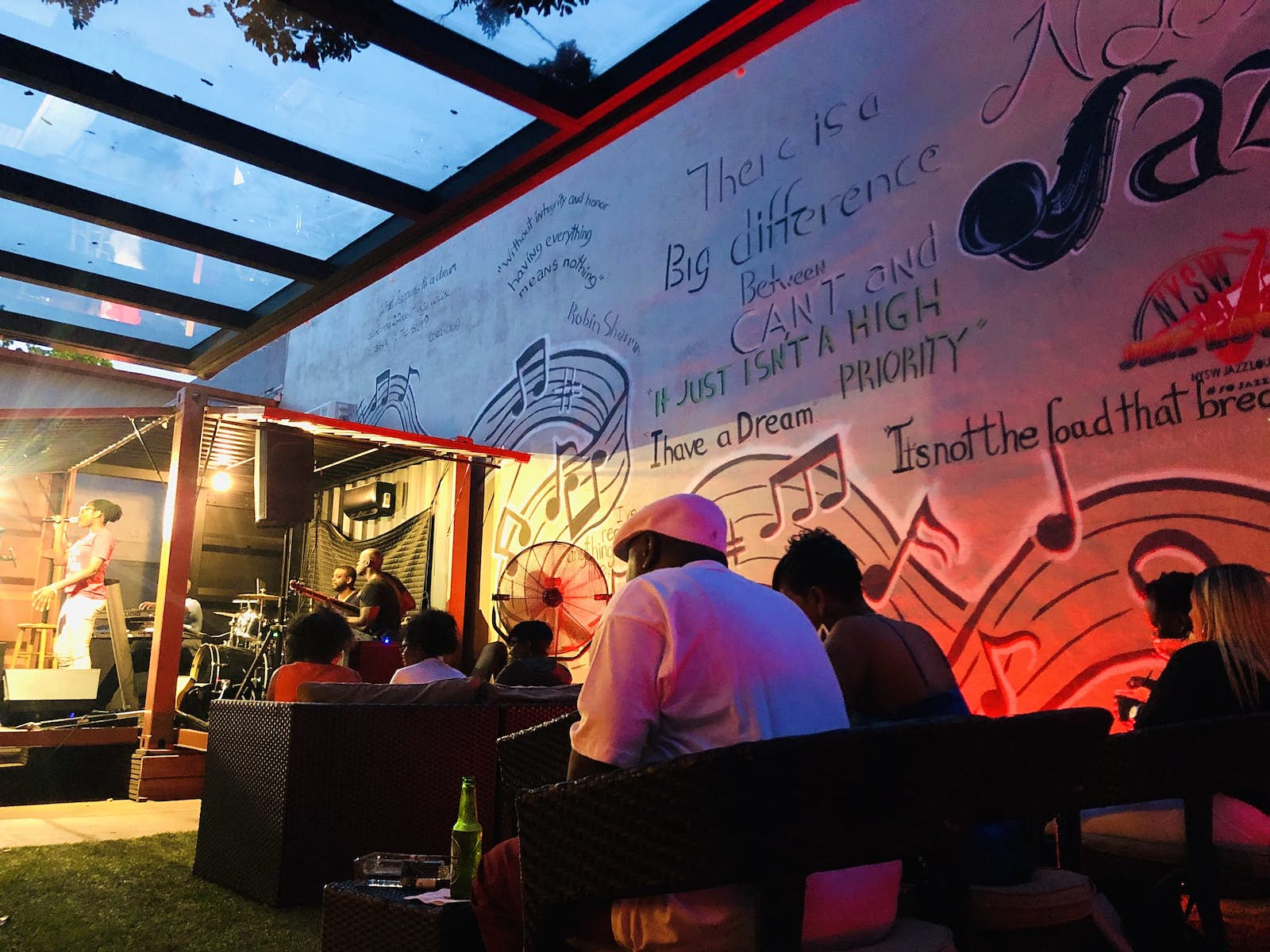 A side view of a jazz singer on the stage at NYSW Jazz Lounge. A perspex roof covers the stage and seating area next to it as patrons drink and enjoy the music. The wall next to them is covered in graffiti.