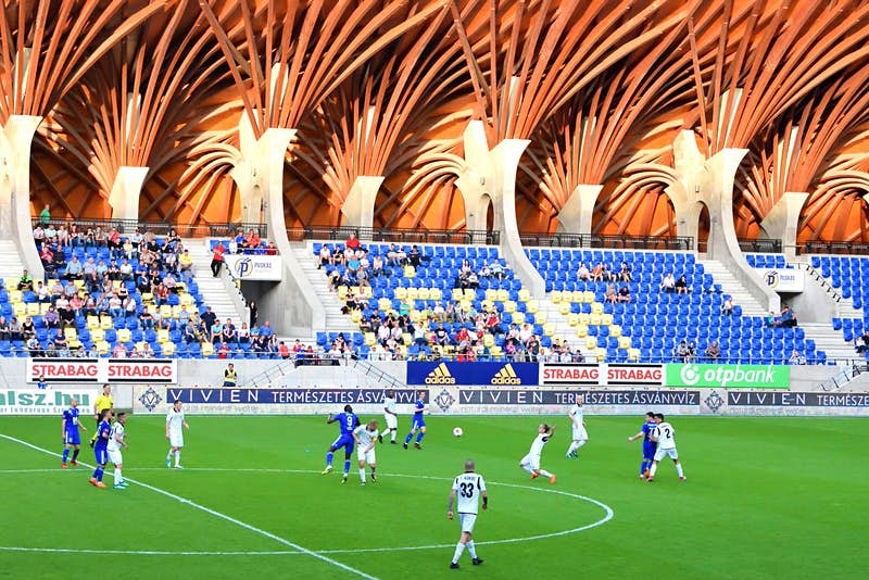 A football match in action at the Pancho Aréna. Beyond the pitch a stand of spectators is visible and above them is the sweeping, timber-beamed roof that makes the Pancho Aréna so distinctive.
