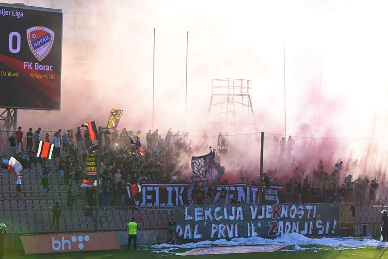 Groups of football fans in a stand during a Čelik home game. Flares have been let off, with the smoke obscuring many of the people in the crowd.
