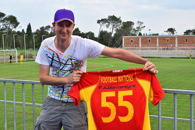Matt stands next to a football pitch in Montenegro, holding a shirt with the number 55 on it