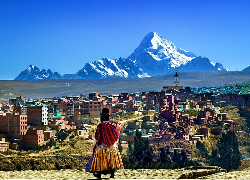 A woman in traditional Bolivian dress walks on a high ridge in La Paz, with the city and a snowcapped mountain in the background. Bolivia.