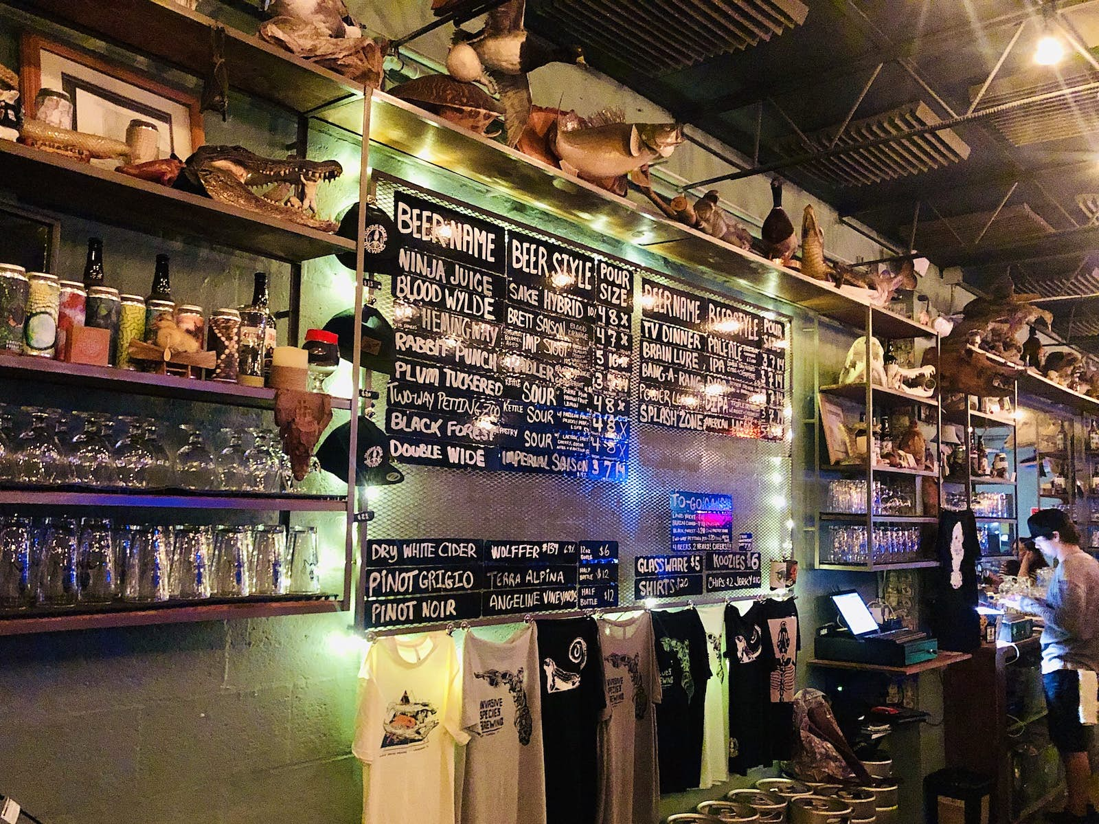 An interior shot of the bar with a wall covered in shelves of liquor, glasses, t-shirts, a beer menu and various items of taxidermy.