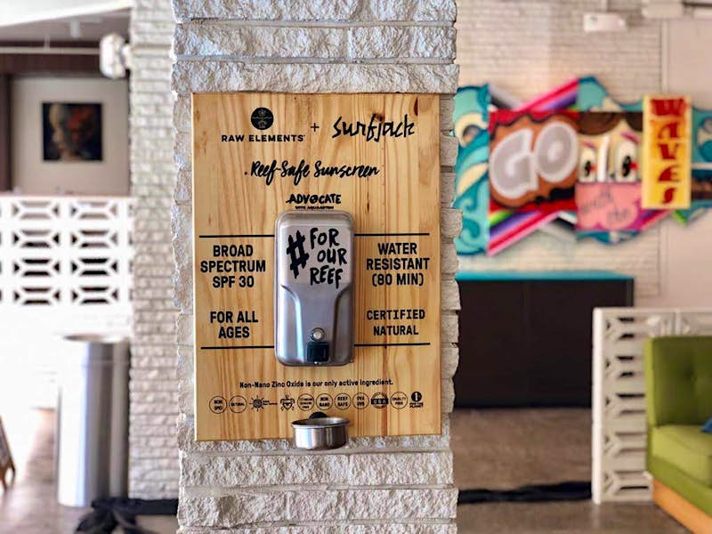 A wooden sign and dispenser offers free reef-safe sunscreen on the wall of a hotel in Hawaii