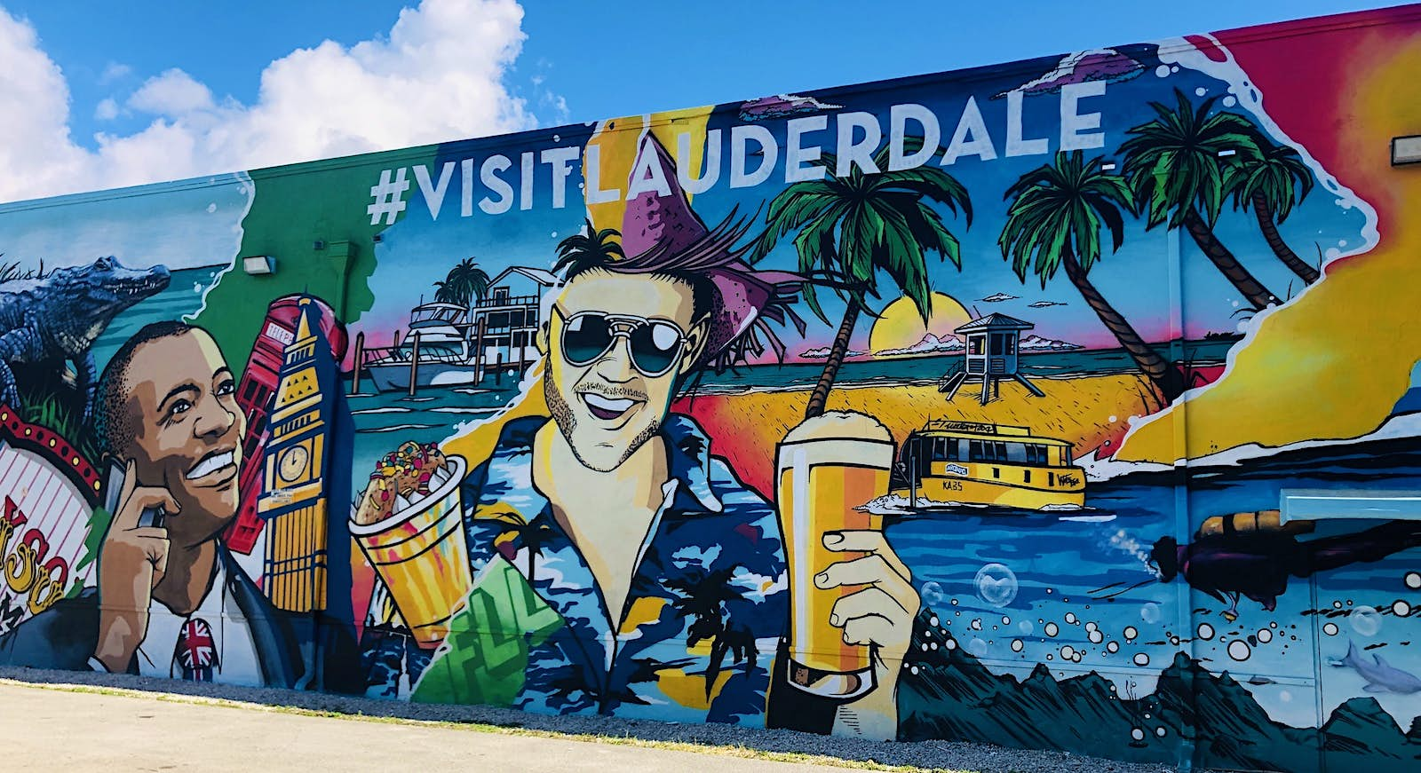 A colorful mural adorns a large wall. It depicts a man with a British flag tie with Big Ben next to him on the left and a man in a Hawaiian shirt and holding a beer is in the centre of the image. Various other images of Fort Lauderdale are included.
