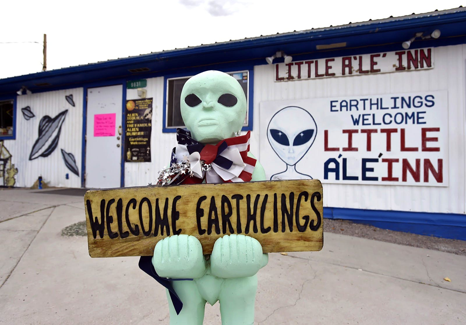 """A plastic green alien holds a sign that says """"welcome earthlings"""" in front of Little A'LE' INN in Nevada; there are plenty of quirky spots along the way to Area 51."""