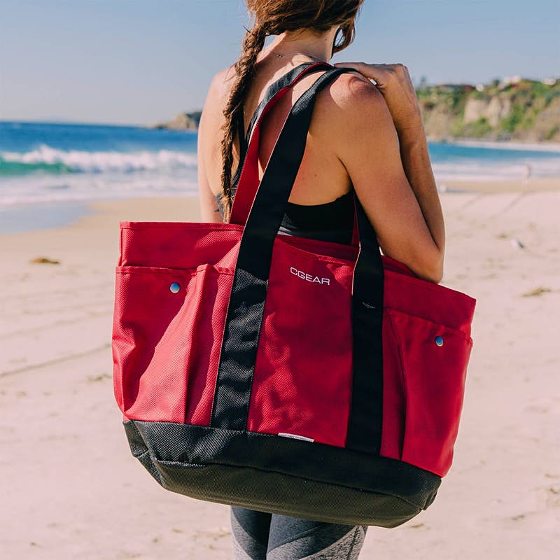 A woman holding a red tote bag on a beach; beach gear