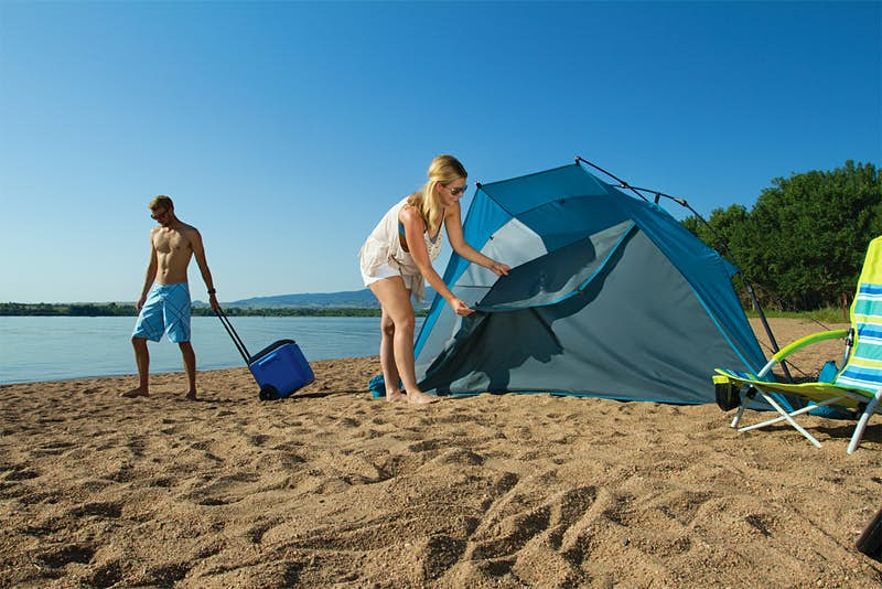 A woman erects a tent on a beach while a shirtless man stares at the ground with a cooler; beach gear