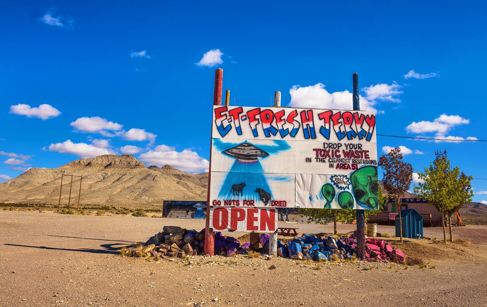 A sign advertising ET Fresh Jerky on the side of a deserted road; area 51