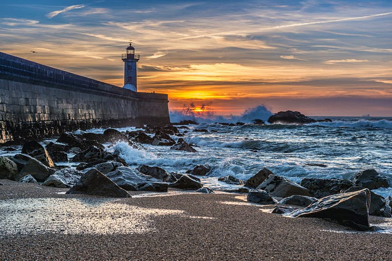 Felgueiras Lighthouse stands at the end of a concrete pier; in the distance the sun sets into a rough ocean, while in the foreground the sea rolls over a beach covered in large stones; free things to do in Porto
