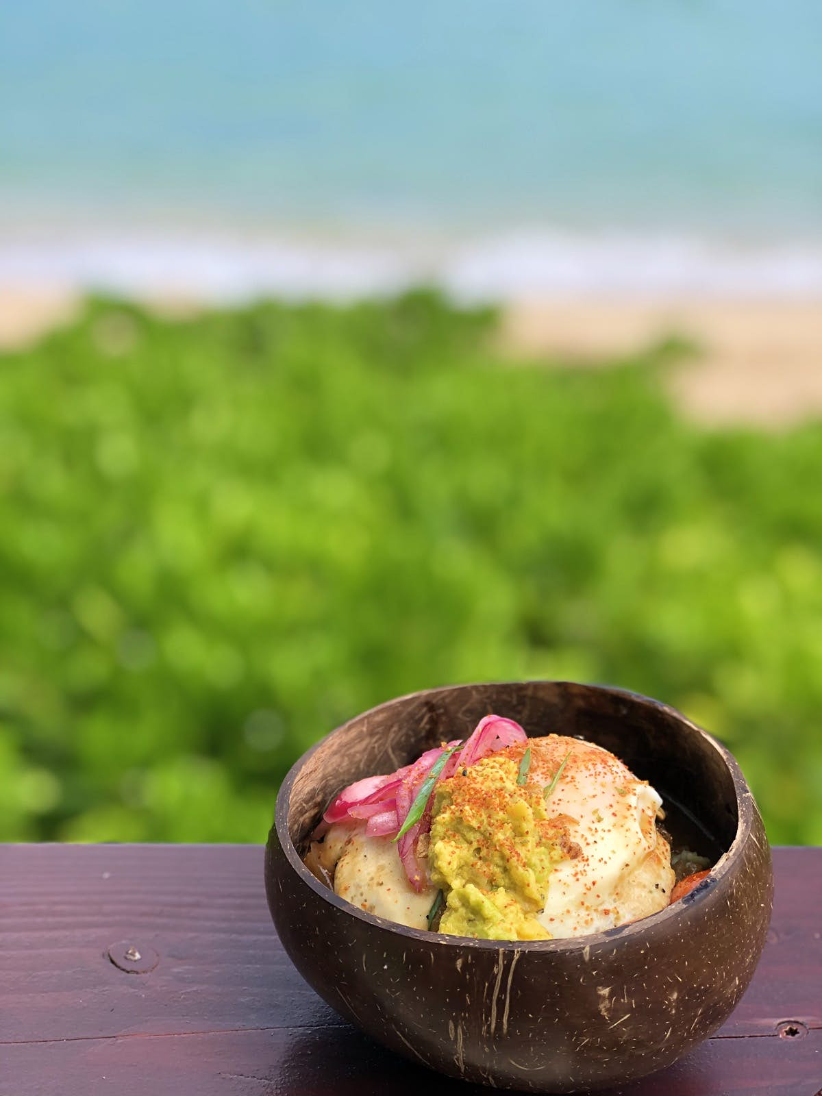 A small brown bowl - possibly a coconut - has some hawaiian food in it. You can see a beach in the background