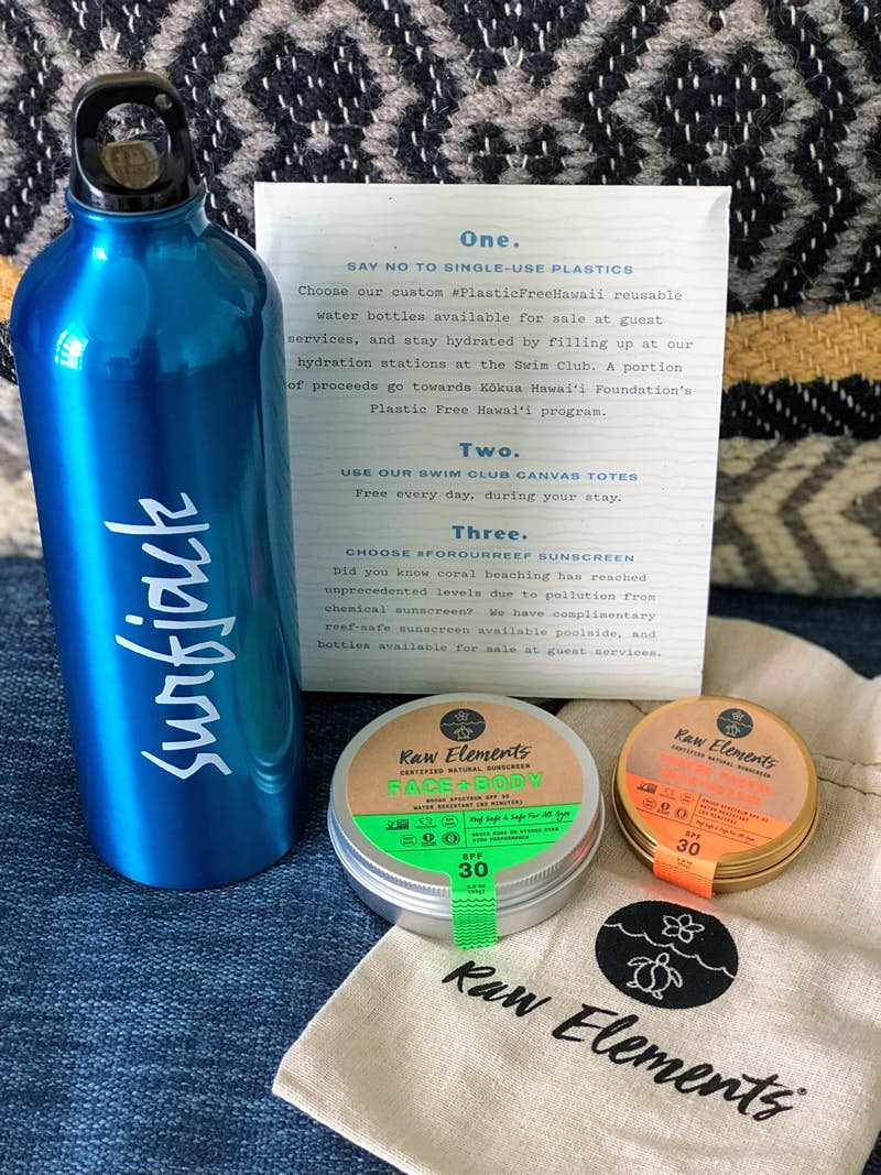 Gear including a reusable water bottle, reef safe sun products and a reusable canvas bag are shown with a letter offering ideas for sustainable travel