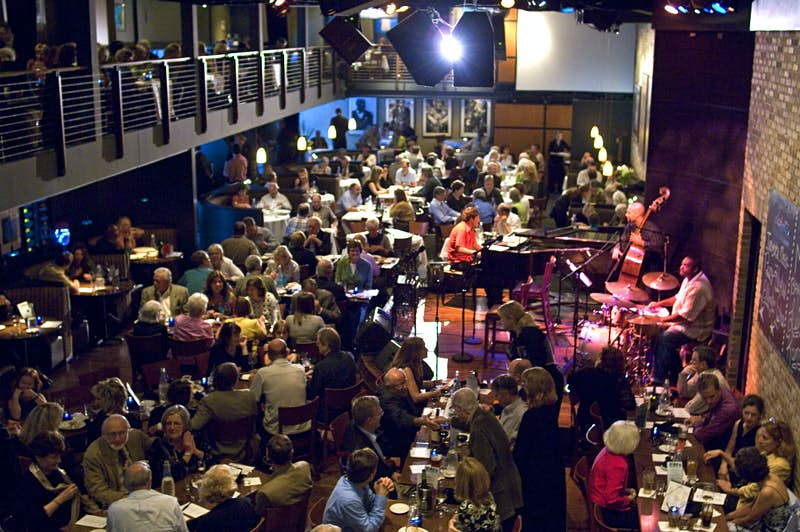 Interior of the Dakota Jazz Club and Restaurant, which is packed with people sitting at tables while a live band plays on an elevated stage