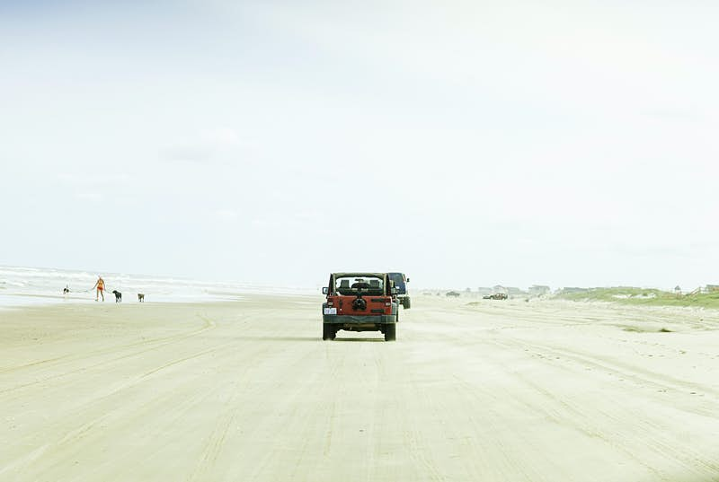 A jeep drives down the centre of Carova Beach, a long white stretch of sand backed by dunes. Nearby a person walks their dogs at the water's edge.