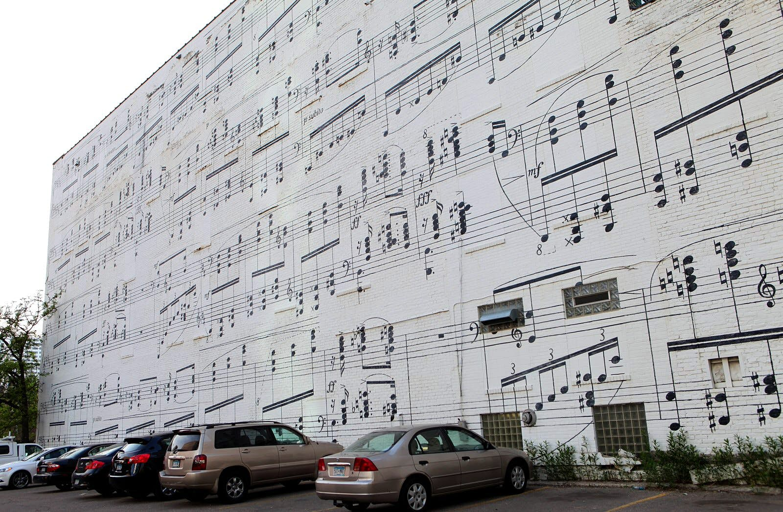 A musical mural on the side of the Schmitt Music Building: the artwork resembles a giant sheet of music, with black music notes painted onto a white background