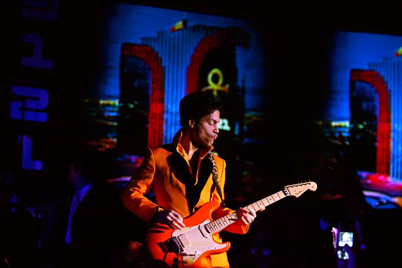 Prince performing at the Rio Hotel in Las Vegas, dressed in a flamboyant orange jacket and playing a matching orange electric guitar