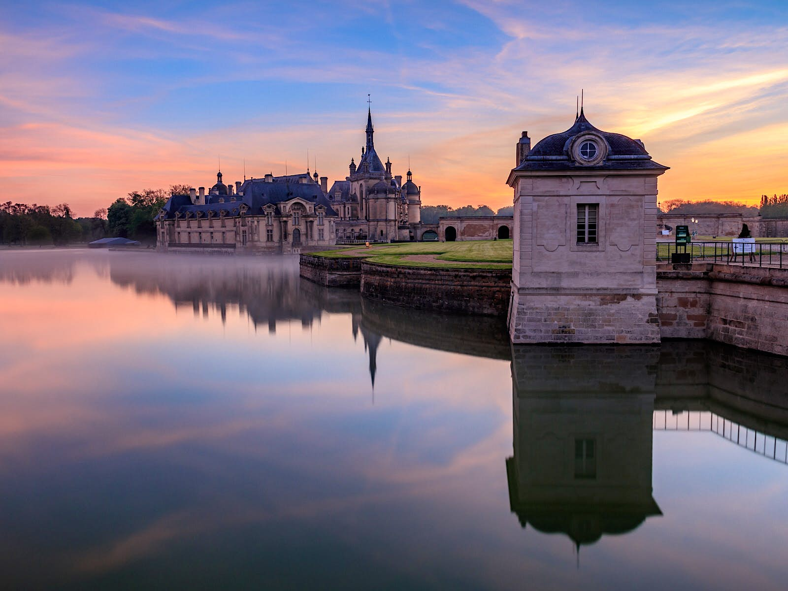 The Château de Chantilly: a large mansion rising from an artificial lake, photographed here at dawn.