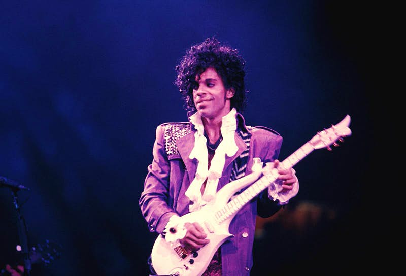Prince performing on stage at the Ritz Club holding a white electric guitar