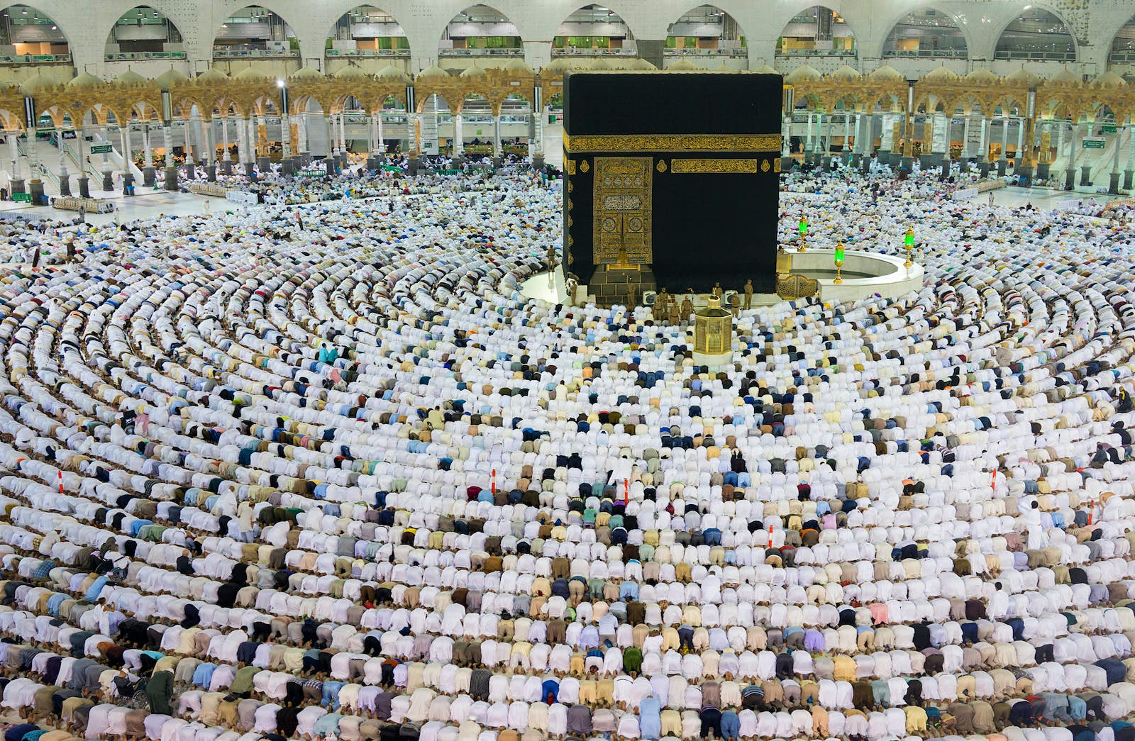 Thousands of Muslims are kneeling in concentric circles around the Kaaba at the The Great Mosque in Mecca. The Kaaba is a large black stone cube with ornate gold details. The majority of the worshippers are wearing white.