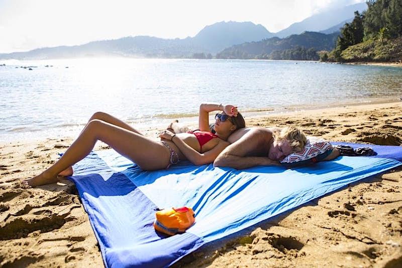 A man and a woman lay on a beach blanket; beach gear