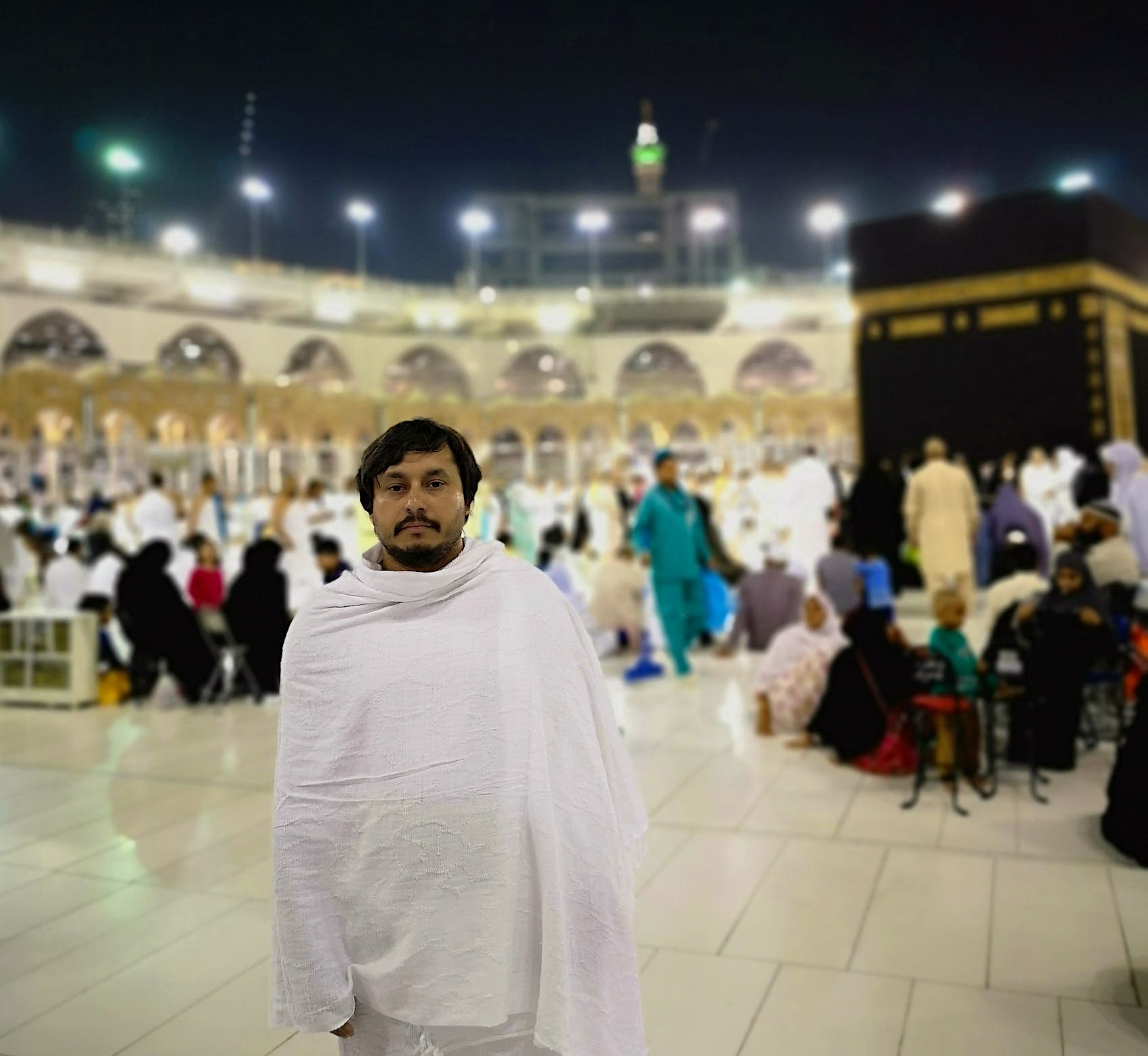 A man in white robe stands facing the camera in front of the Kaaba in The Great Mosque in Mecca. A large group of pilgrims are in the background behind him, sitting, standing and talking.
