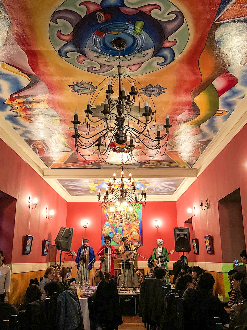 Bolivian musicians play in a red room with a colorful mural on the ceiling. La Paz, Bolivia.
