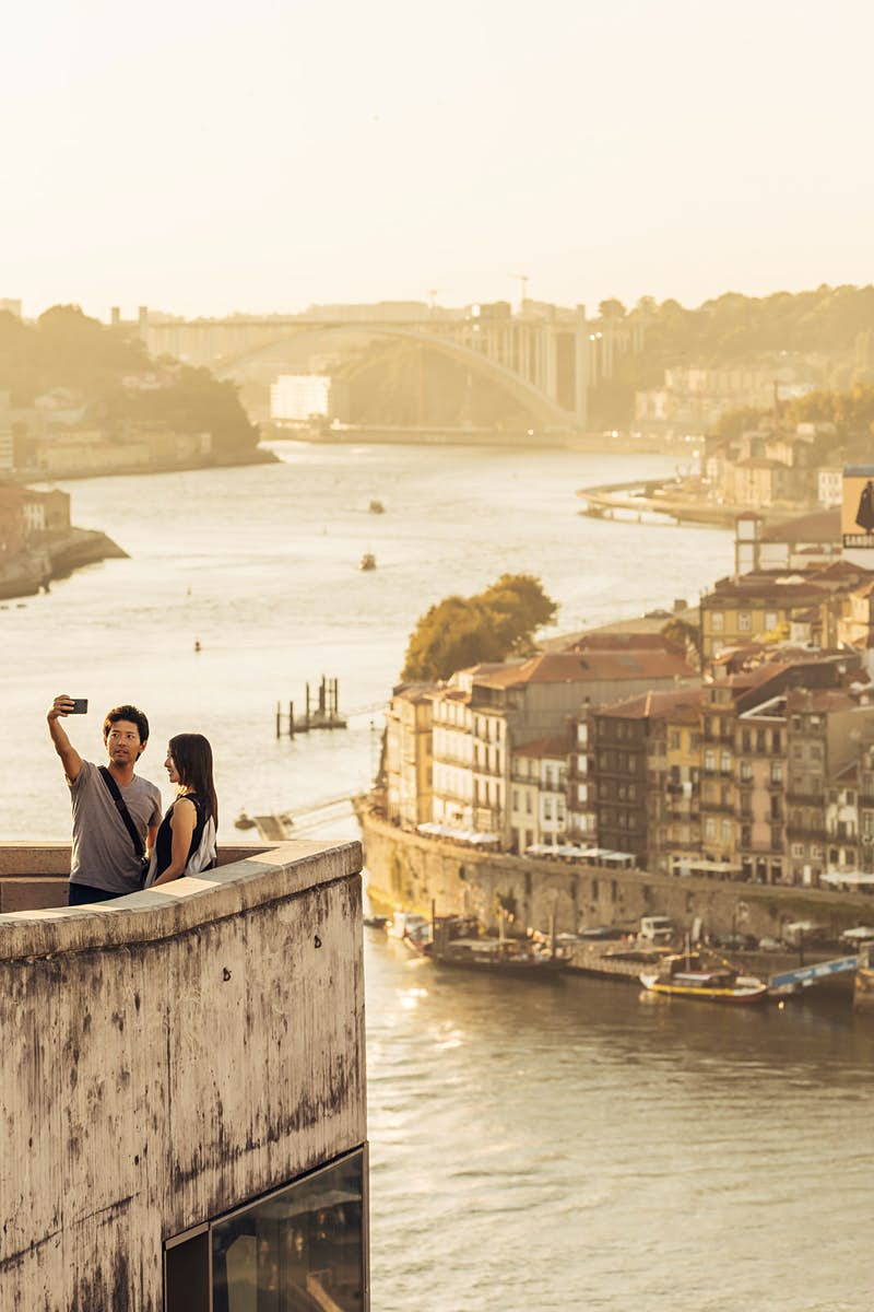 A couple takes a selfie standing on a stone balcony at the Jardim do Morro; spectacularly, the city of Porto is spread out below them on the River Douro; free things to do in Porto