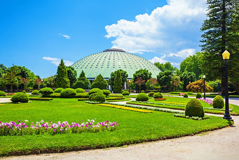 The foreground is filled with beautifully manicured lawns, flowerbeds, trees and shrubs, while in the distance is a large green dome rising above the treeline; free things to do in Porto