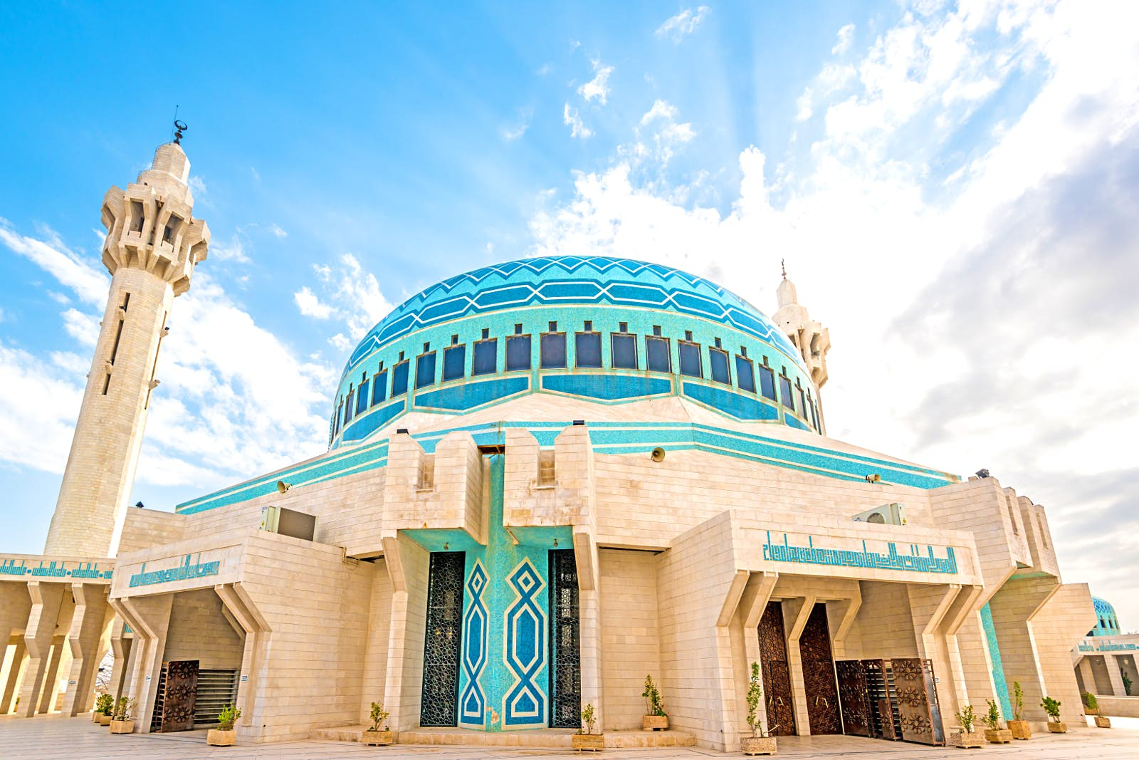 Shot with a wide-angle lens, this image looks from the ground up at the large blue dome and towering minarets; the lower part of the mosque is tan coloured with blue mosaic tiles; Free things to do in Amman, Jordan