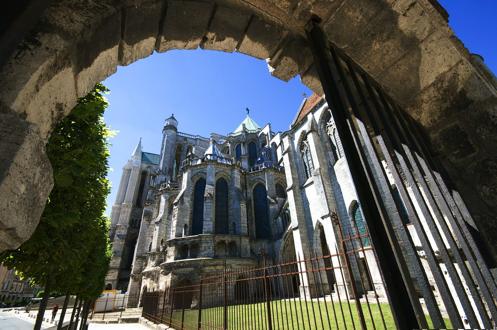 Chartres' Romanesque-style Cathédrale Notre Dame viewed from beneath a grey stone arch.