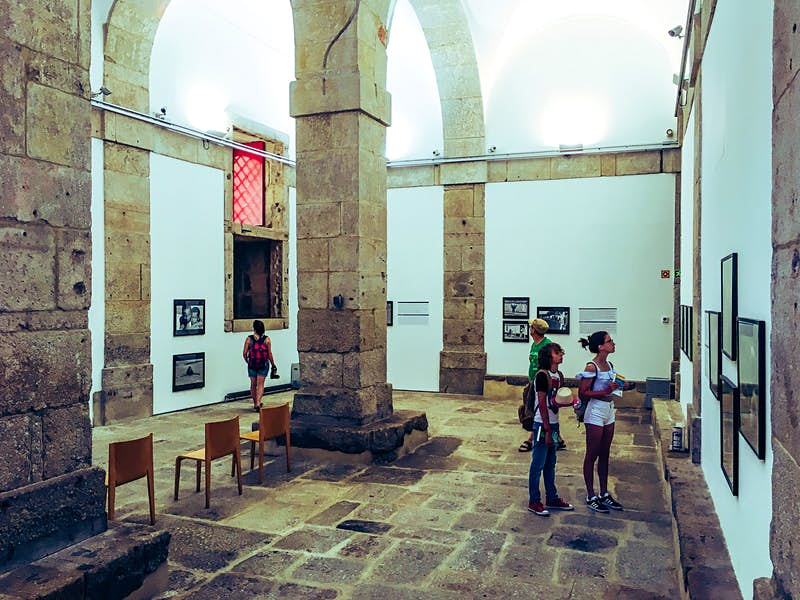 Four people look at various photo exhibits within a large white-washed room within an old prison; large stone columns and arches dominate the space; free things to do in Porto