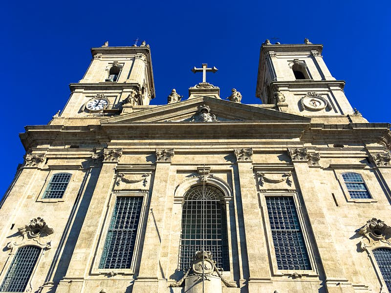 Looking directly up the facade of Igreja da Lapa, the two towers poke up into the cobalt-coloured sky; the church is made of grey sandstone; free things to do in Porto