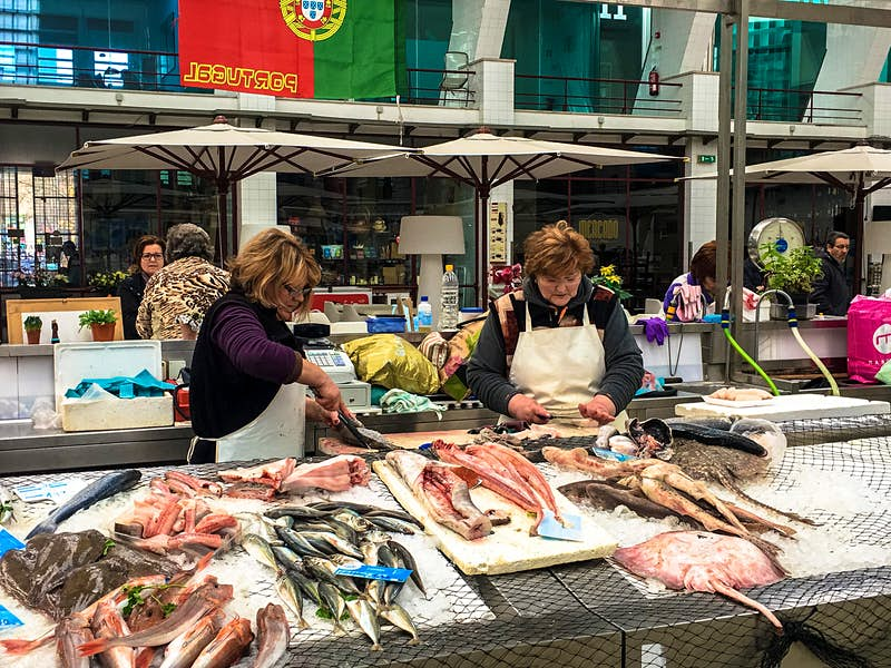 Two women working at a fishmonger stall clean fish at Mercado de Matosinhos; visiting this local market is one of the best free things to do in Porto
