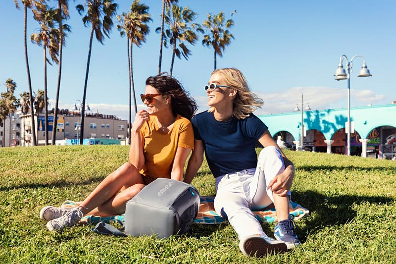 Two women in a sunny park with a backpack cooler on a beach towels, with palm trees in the distance; beach gear