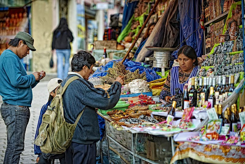 A vendor at the Mercado de las Brujas talks with a man about her wares. The stall is lined with talismans and herbs. La Paz, Bolivia.