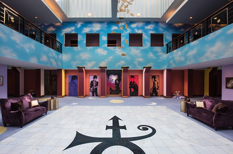 Prince's symbol is in the middle of a white floor in black, as images of the singer at various points in his career look out from cubbyholes in a sky-blue wall with clouds and two balconies on either side of the atrium