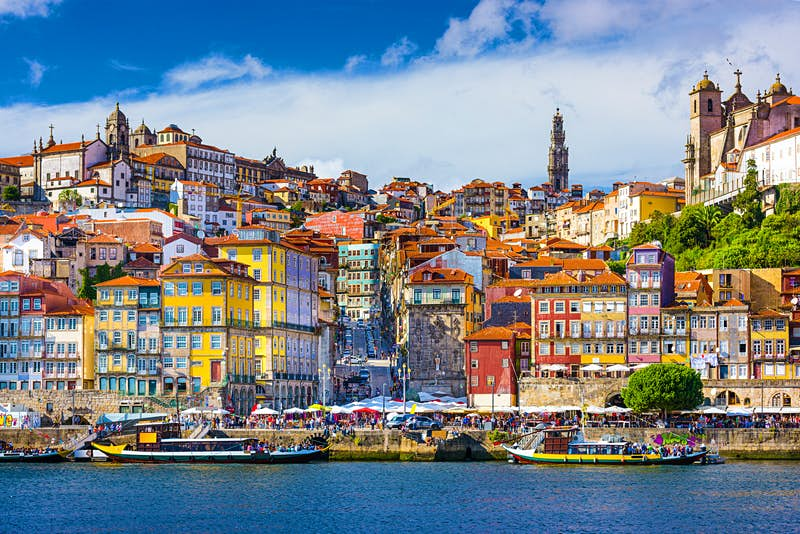 Looking across the River Douro, the colourful buildings of Porto's old town climb up a hill; bursting from the top of the hill is the large tower of Torre dos Clérigos; attending a concert across the street from the tower is one of the best free things to do in Porto
