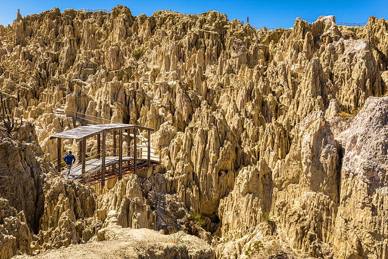 A person crosses a wood bridge among jagged geological formations in Valle de la Luna. La Paz, Bolivia.