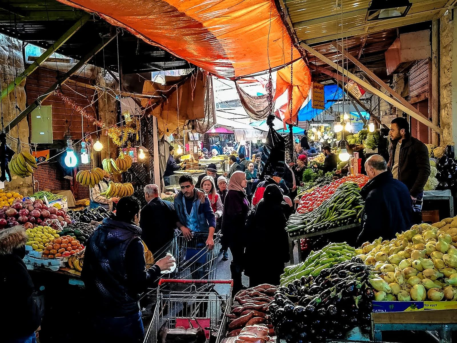 Fruit and vegetables are piled high on both sides of a narrow walkway under a covered market; shoppers push carts or carry bags, while sellers stand behind their goods on raised platforms; Free things to do in Amman, Jordan