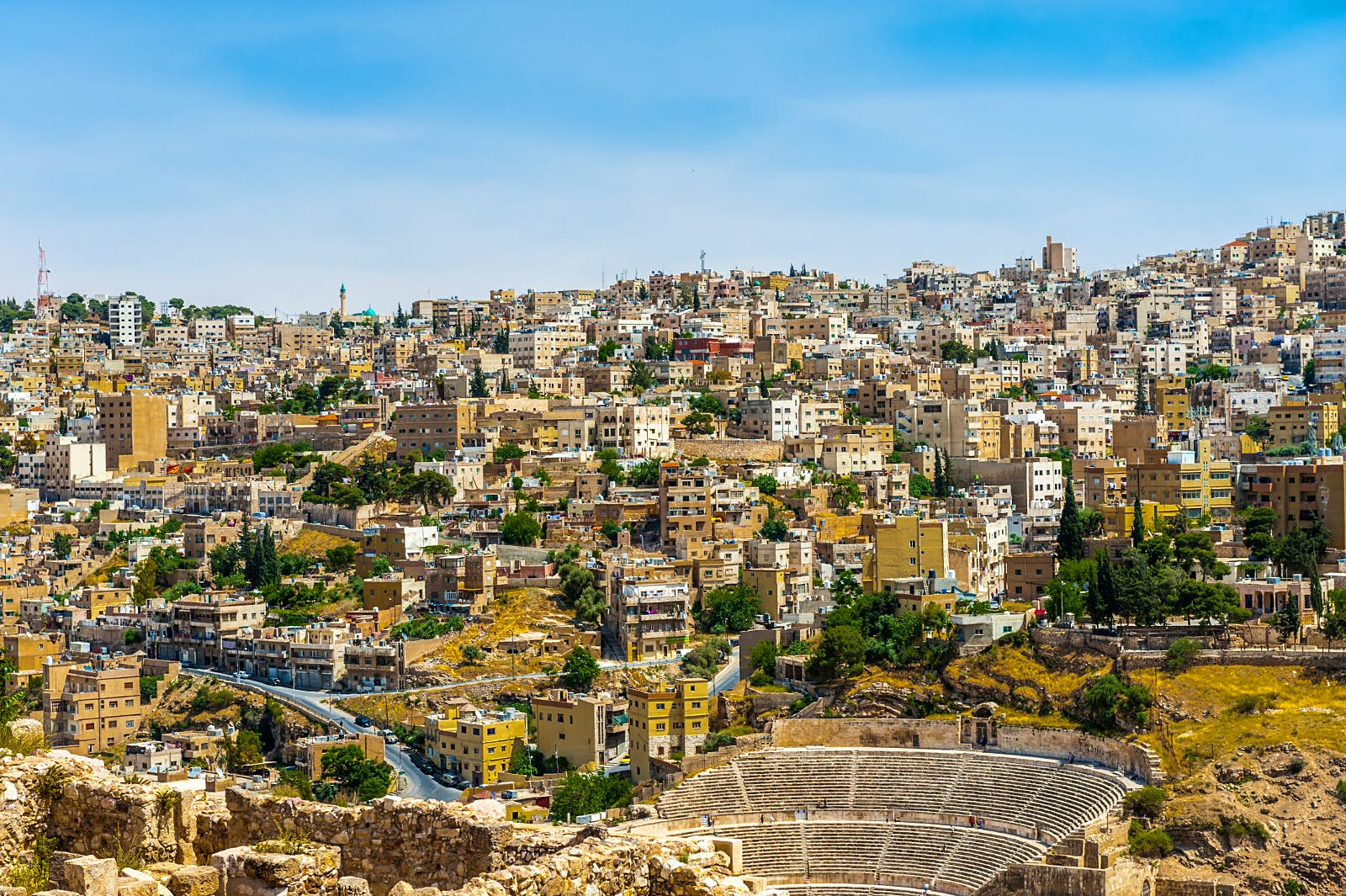 In front of the city that seems perched on a hillside is the Roman Theatre, with its semi-circular seats arching around its centre stage; Free things to do in Amman, Jordan
