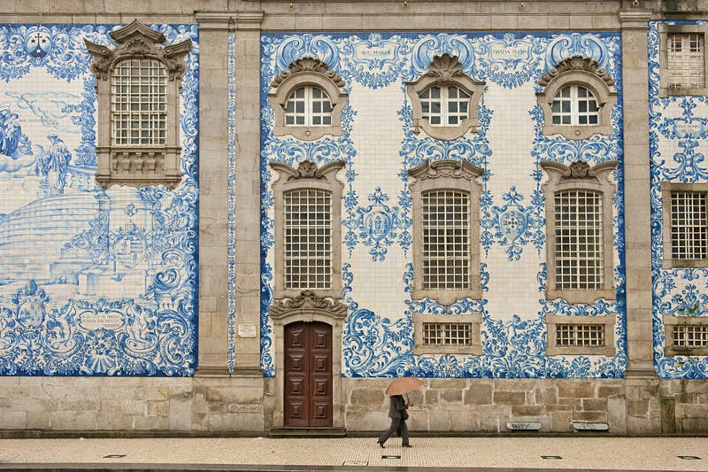 A stunning facade of blue and white tiles cover the Igreja do Carmo in Porto; a person walks in front of this grand two-storey building. Seeing these tiles is one of the best free things to do in Porto