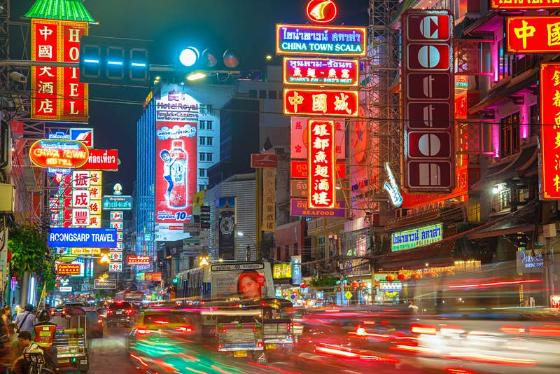 Traffic on Yaowarat Road passes below neon-lit signs in the Chinatown district at night.