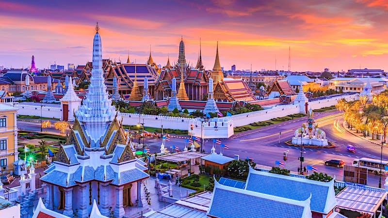 The sun sets over Wat Phra Kaew (Wat Phra Si Rattana Satsadaram or Temple of the Emerald Buddha) and the Grand Palace