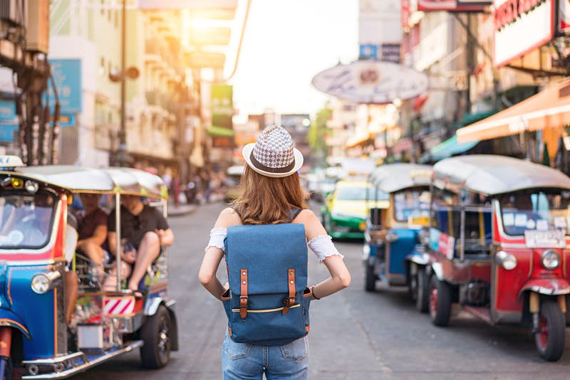 The back of a young woman walking along the pedestrian street in the evening in Bangkok, Thailand; travelers, tourists and tuktuks line the street.