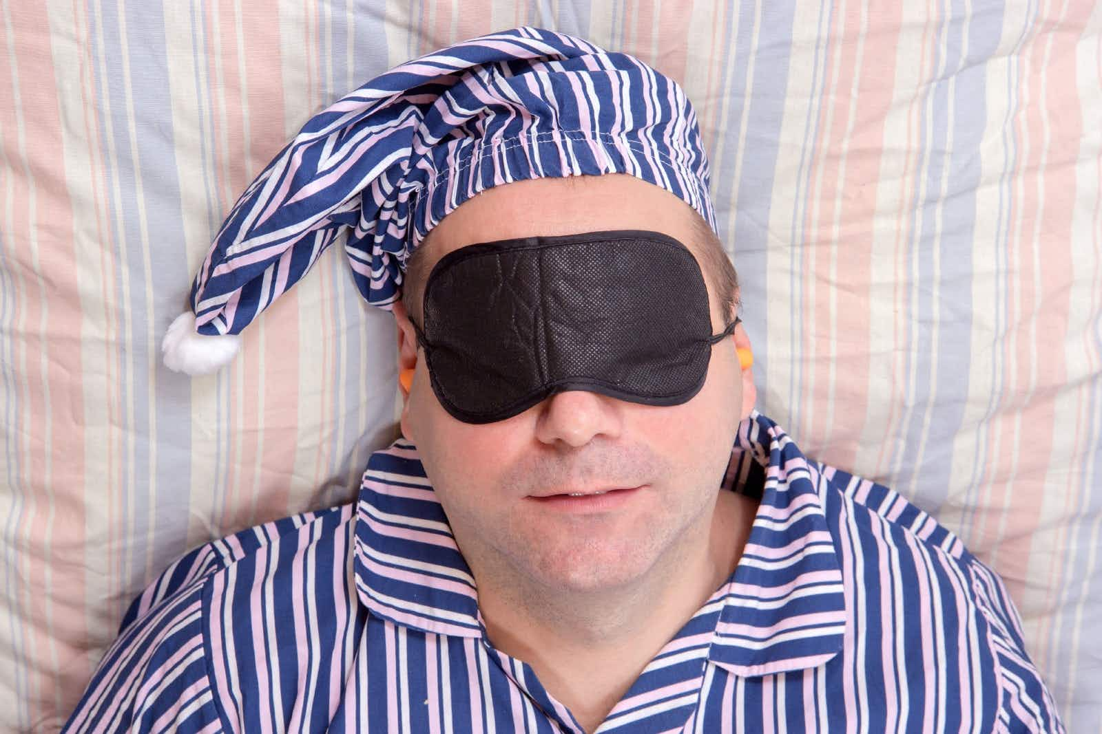 A middle-aged man dressed in blue and white striped pyjamas and matching hat reclines on a striped bedsheet with a black eye mask over his face and ear plugs.