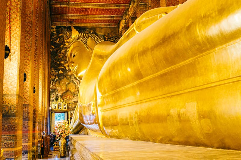 Within a small door at the distant end of a Thai temple (Wat Pho) stand a few visitors who are dwarfed by the gargantuan 46m-long Reclining Buddha statue; its feet are off the end of the picture, with its legs visible moving up towards its waste and towering head; the walls and ceiling of the temple are rich in gold, red hues and elegant designs.