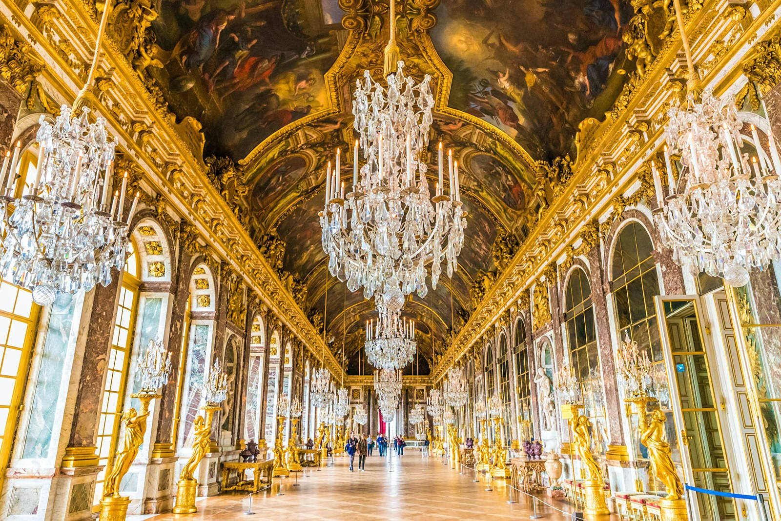 Interior of the Château de Versailles: an extremely grand corridor with gold statues, huge windows and ornate, crystal chandeliers