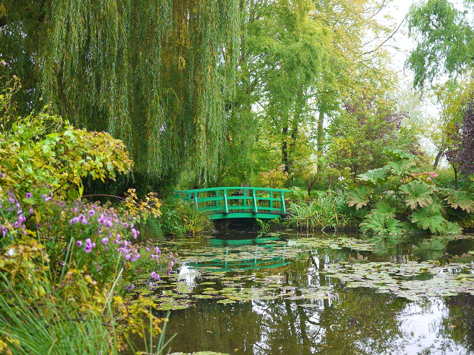Claude Monet's Garden of Giverny, with the iconic green Japanese bridge reflecting in the water lilies pond.