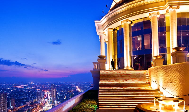 A Roman-looking circular stone building with large columns is lit up brilliantly from below; to the left, down in the distance is the teeming city of Bangkok
